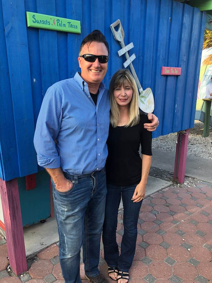 reverend john roberts and wife stand casually at a restaurant smiling at camera