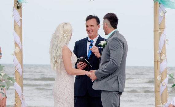 reverend john roberts marries couple on the beach under an arch